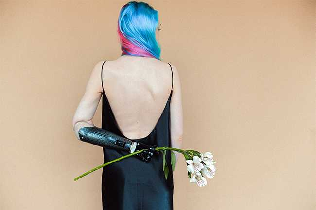 A person with bright blue and pink hair, facing a tan wall, with their arm behind their back and holding a flower with their prosthetic hand