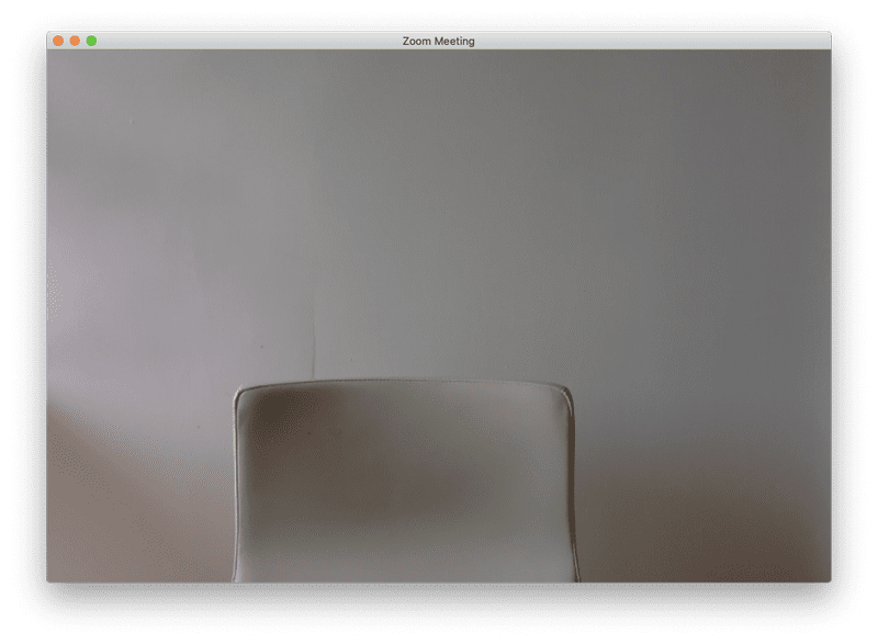 Screen shot of a Zoom meeting with an empty chair against a plain wall