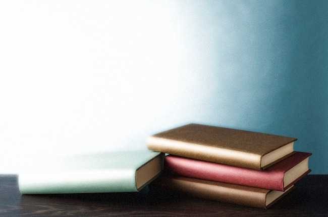 A stack of two plain gold books and one red book, with a green book leaning against the stack